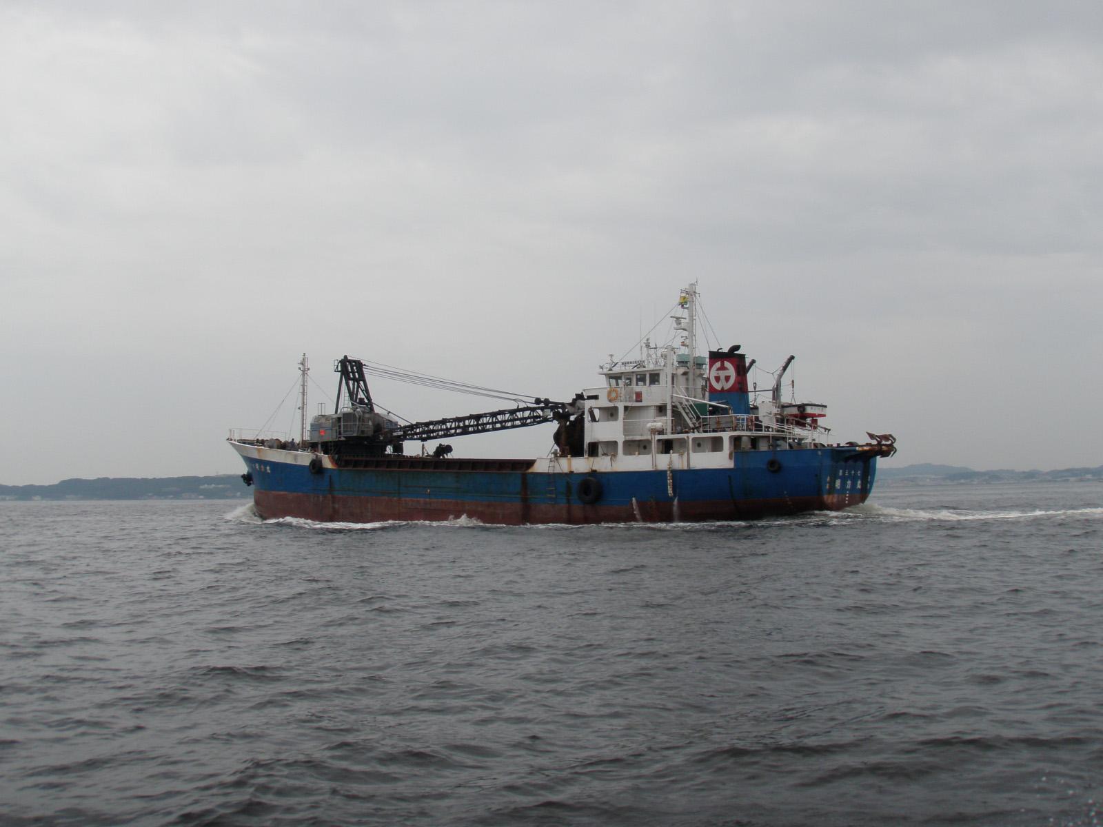 左に航行中のクレーンを積んだ作業船の写真